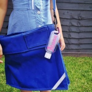 Personalised Hand Sanitiser Bottle Clipped Onto A School Book Bag